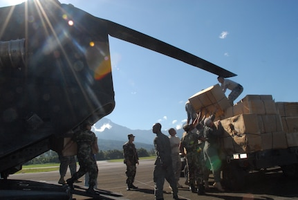 LA CEIBA, Honduras - Soldiers and Airmen from Joint Task Force-Bravo at Soto Cano Air Base, Honduras, offload donated wheelchairs from a CH-47 Chinook helicopter here Dec. 28.  The hand-crank wheelchairs were donated to isolated villages along the Miskito Coast of Honduras.  The Alabama non-profit organization Missions Unlimited contacted the U.S. Agency for International Development to coordinate the donation. (U.S. Air Force photo by Tech. Sgt. Sonny Cohrs)