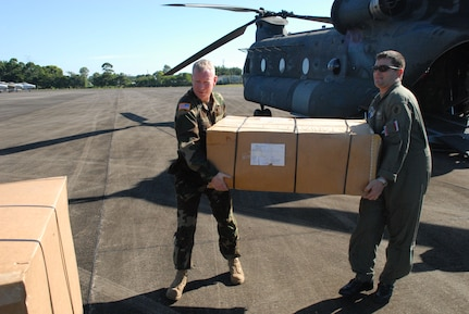 LA CEIBA, Honduras - (Left) Army Lt. Col. Todd Conyers, 1st Battalion, 228th Aviation Regiment commander, and Army Staff Sgt. Daniel Glick, also with the 1/228, offload donated wheelchairs from a CH-47 Chinook helicopter here Dec. 28.  The hand-crank wheelchairs were donated to isolated villages along the Miskito Coast of Honduras.  The Alabama non-profit organization Missions Unlimited contacted the U.S. Agency for International Development to coordinate the donation. (U.S. Air Force photo by Tech. Sgt. Sonny Cohrs)