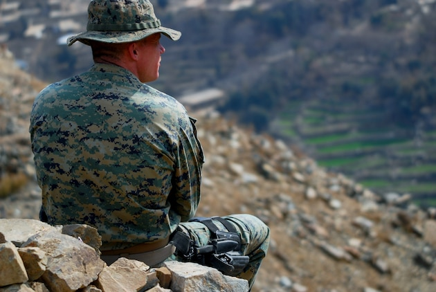 Marine 1st Sgt. Matthew S. Seamans, of Shorewood, Minn., sits at an observation point on top of a mountain overlooking a border checkpoint 500 meters below in eastern Konar Province, Afghanistan. Seamans is an embedded training team mentor deployed to Afghanistan from Okinawa, Japan, to work with the Afghan National Army. Photo by Marine Staff Sgt. Luis P. Valdespino Jr.