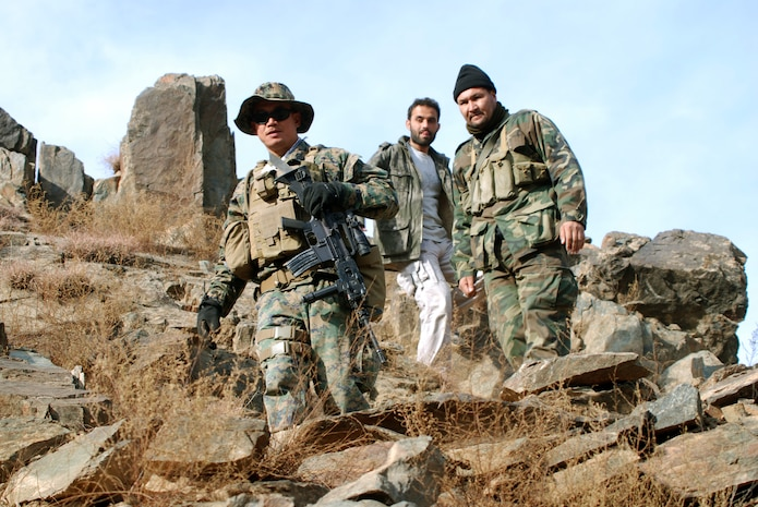 Petty Officer 1st Class Reynaldo S. Datu is followed by Afghan National Army Maj. Abdul Latif, executive officer of 3rd Kandak (Armored), 3rd Brigade, 201st ANA Corps, and Maroof, an interpreter, as they make their way back from an observation point on top of a mountain to a border checkpoint 500 meters below in eastern Konar Province, Afghanistan. Datu is part of an embedded training team deployed to Afghanistan from Okinawa, Japan, to work with the ANA. Photo by Marine Staff Sgt. Luis P. Valdespino Jr.