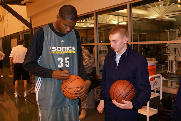 Seattle SuperSonics rookie Kevin Durant signs a basketball for Senior Airman Troy Bame, 62nd Operations Support Squadron,Wednesday at the Sonics practice facility in Seattle. Four McChord Airmen and servicemembers from other branches of the militarywere invited to the facility to watch a practice, meet and eat lunch with the players, and attend Wednesday night's gameagainst the New Orleans Hornets.