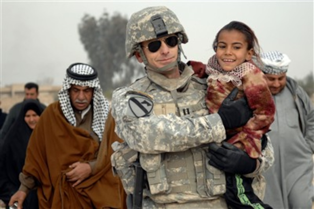 Capt  Keith Koppenhaver carries a young Iraqi girl