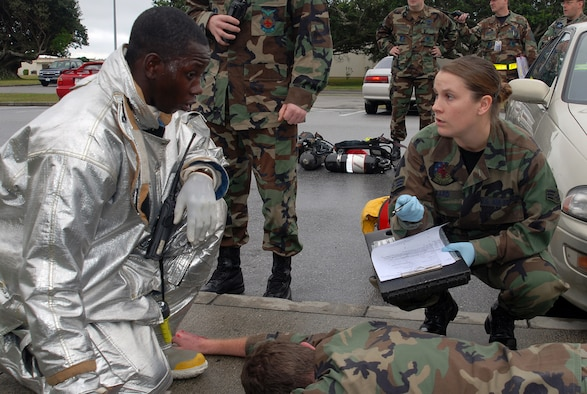 Senior Airman Ashley Sard, 18th Medical Operations Squadron, gets victim information from a firefighter following a simulated explosion at the Marshall Dining Facility during Local Operational Readiness Exercise Beverly High 08-3 at Kadena Air Base, Japan, Jan. 7, 2007. The 18th Wing exercise from Jan. 7 to 11 tests the wing's ability to respond in contingency situations.   (U.S. Air Force photo/Tech. Sgt. Dave DeRemer)