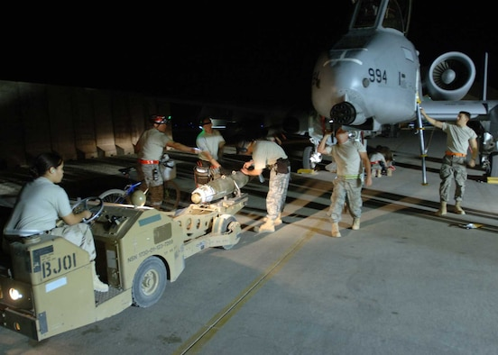 "A 438th Air Expeditionary Group weapons loading team prepares to mount a Joint Direct Attack Munition to an A-10C Thunderbolt II using an MJ-1 ""jammer"" vehicle here. The Airmen made history in Iraq when their upgraded A-10s successfully employed JDAMs in combat. Because the weapon is guided to targets by pinpoint GPS coordinates, experts here say it is 100 percent more accurate than munitions previously employed on the A-10C Thunderbolt II, dramatically improving precision and reducing fratricide. The Airmen are deployed from the 175th Wing, Maryland Air National Guard, located in Baltimore, Md. (U.S. Air Force photo/Tech. Sgt. D. Clare)"