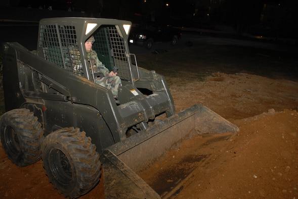 Staff Sgt. Daniel Rothenhoefer, 18th Civil Engineer Squadron, drives a bobcat as he builds a berm to hold 10,000 gallons of fuel during a Local Operational Readiness Exercise Beverly High 08-3 scenario at Kadena Air Base, Japan, Jan. 8, 2007. The 18th Wing conducted the exercise from Jan. 7 to 11 to test Airmen's ability to respond in contingency situations. (U.S. Air Force photo/Staff Sgt Chrissy FitzGerald)