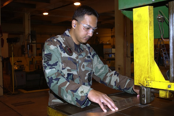 Staff Sgt. Joseph Baza, 36th Maintence Squadron, cuts a piece of sheet metal with a banding saw. Sergeant Baza was one of fifty Airmen in the Air Force to be selected for the Scholarships for Outstanding Airmen program. (U.S. Air Force photo/Airman 1st Class Carissa Morgan)