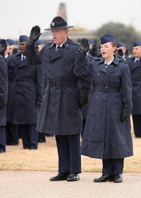 Re-enlistee, Tech. Sgt. Robert Rayburn, a military training instructor with the 331st Training Squadron, takes the Oath of Enlistment alongside his daughter, Airman Marlana Rayburn, during a basic military graduation parade at the Lackland Parade Grounds Jan. 4. (USAF photo by Robbin Cresswell)