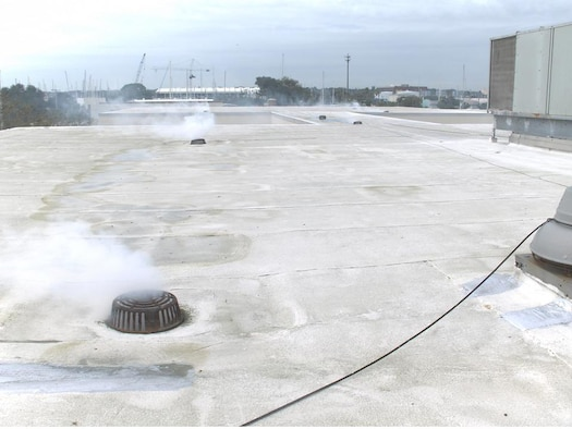 Smoke escapes roof drains during a smoke test conducted at Tyndall Air Force Base.  (Photo Courtesy of the 325th Civil Engineer Squadron)