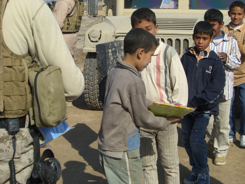ALI AIR BASE, Iraq -- Iraqi children wait in line to receive school supplies from an Air Force Special Agent Dec. 29 in a village near An Nasiriyah. In just over a month, Airmen of the 407th Air Expeditionary Group collected thousands of school supply items, soccer balls, stuffed animals and toys from back home for the base's Operation Iraqi Child program. (Courtesy Photo)