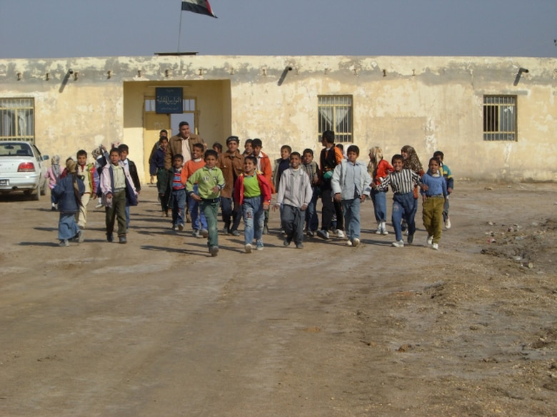 ALI AIR BASE, Iraq -- Iraqi children run with excitement toward Air Force Special Agents who brought school supplies and toys Dec. 29 to the village near An Nasiriyah. In just over a month, Airmen of the 407th Air Expeditionary Group collected thousands of school supply items, soccer balls, stuffed animals and toys from back home for the base's Operation Iraqi Child program. (Courtesy Photo)