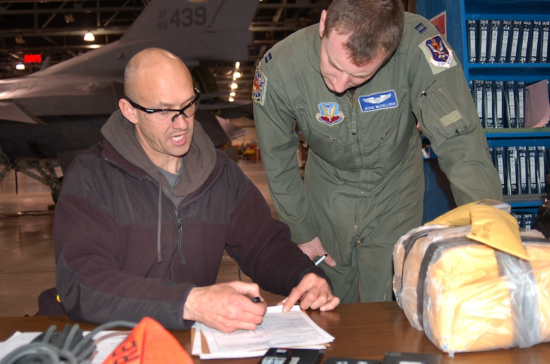Final paperwork to send Aircraft 80-0172 to Moody AFB, Ga., is discussed by Andrew Selph, A-10 Flight Test, and Capt. Jesse McCulloch. The aircraft is the 100th to receive the Precision Engagement modification, installed by the 571st Aircraft Maintenance Squadron. (U.S. Air Force photo by Bill Orndorff)