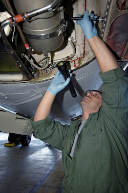 James Mattingly, an aerospace propulsion craftsman from the 932nd Maintenance Group, 932nd Airlift Wing, re-installs a combustion chamber on an auxiliary power unit on a C-9C Skytrain aircraft in hangar one, Scott AFB, Ill.   U.S. Air Force photo/Tech. Sgt. Tony R. Tolley