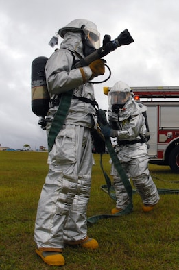Airmen 1st Class Mark Maslawski and Hector Garcia prepare to decontaminate potential victims of a suspicious package during a Disease Containment Exercise Jan. 15.  The Airmen are fire apprentices from the 36th Civil Engineer Squadron. (U.S. Air Force photo/Airman 1st Class Jonathan Hart)