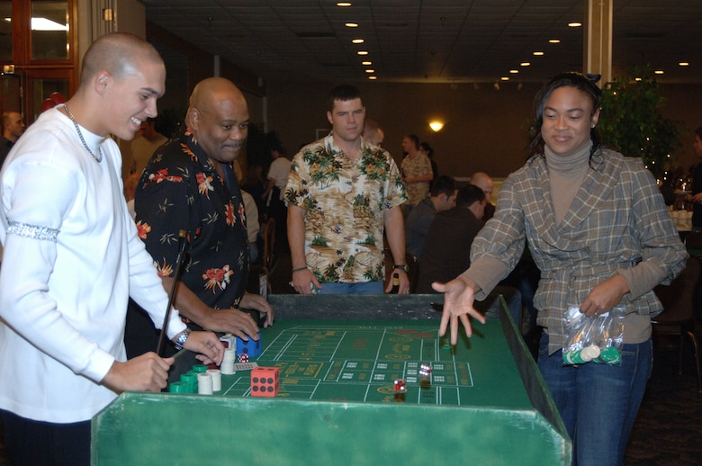 Tina Franklin, wife of Maj. Ben Franklin, 14th Medical Operations Squadron, rolls the dice at the craps table as others look on Friday at Monte Carlo Night at the Columbus Club. (U.S. Air Force photo by Airman 1st Class Danielle Hill)
