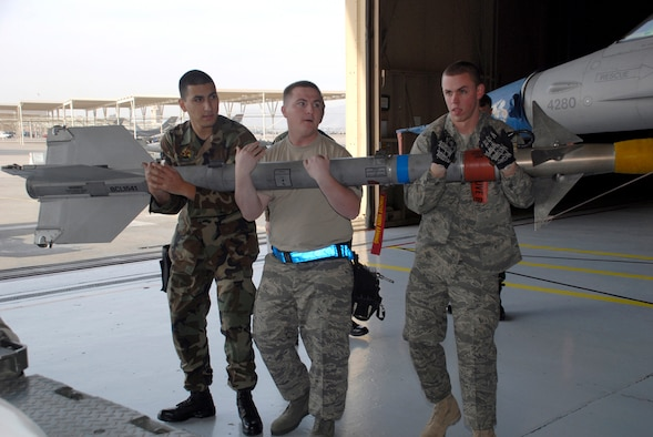 (From left) Airman 1st Class Marcus Irizarry, Staff Sergeant William Massey, and Senior Airman Austin Ward, all members of a weapons load crew from the 62nd Aircraft Maintenance Unit, carry a missile to an F-16 during the Load Crew Competition Jan. 10. In order to win this competition, each crew in the competition must try to assemble weapons on one side of the jet before the other crew finishes. (U.S. Air Force photo by Airman 1st Class Tracie Forte)