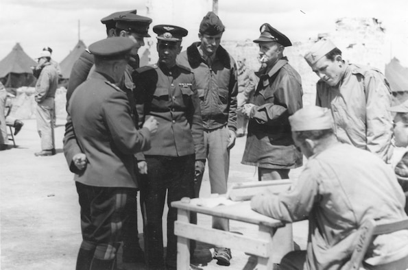 In the ruins of a hangar at Poltava, Gen. Porminov and Gen. Walsh listen to a pilot's report after the mission to Galati. The officer in the center is Capt. Henry Ware, interpreter from Gen. Deane's staff. (U.S. Air Force photo)