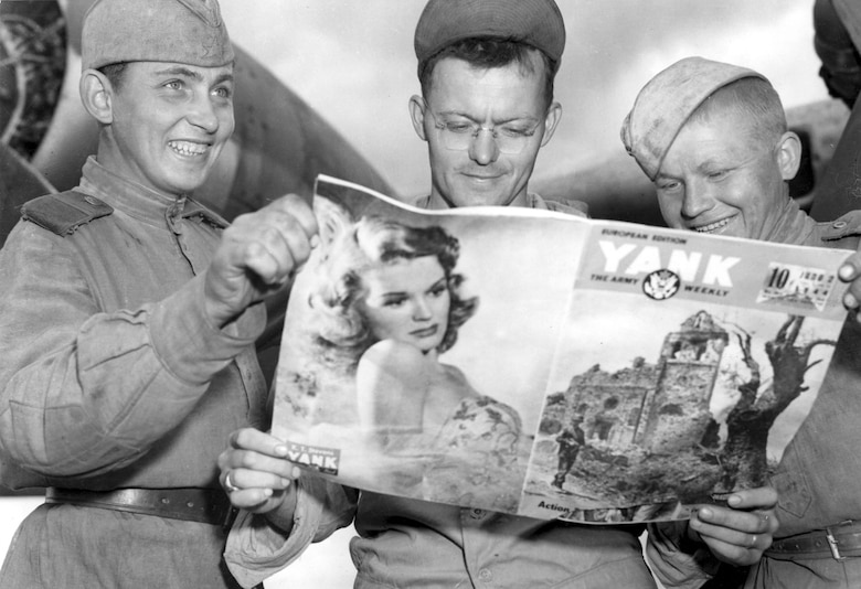 "Two unidentified Russian soldiers look at Cpl. Thomas Klopack's ""Yank"" Magazine. (U.S. Air Force photo)"