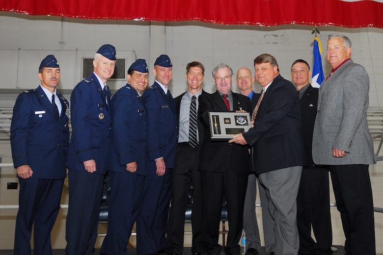 Mr. Klingaman, (fifth from right) was presented a dagger plaque by all of the former 6th SOS commanders. (Left to right) Col. Jim Sikes, Col. Norm Brozenick, Col. John Alvarez, Lt. Col. Dave Tabor, current 6th SOS commander, retired Lt. Col. Eric Huppert, retired Col. Scott Pugmire, retired Maj. H. Scott Murphy, who is not a former 6th SOS commander but the holder of 6th SOS Coin #1, retired Lt. Col. Monty Sexton and retired Col. Steve Whitson. (Courtesy photo)