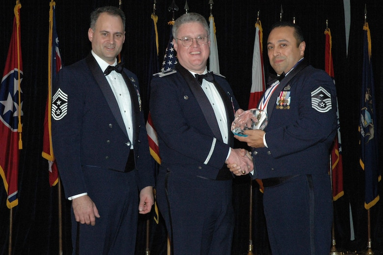 MCGUIRE AIR FORCE BASE, N.J. -- Senior Master Sgt. Gil Morales, right, of the 35th Aerial Port Squadron receives the 514th Air Mobility Wing First Sergeant of the Year 2007 Award from Commander Col. James L. Kerr, middle, and Command Chief Master Sgt. Michael J. Ferraro, left, Jan. 12 during the Reserve wing's 8th annual awards banquet. (U.S. Air Force photo/Senior Airman William P. O'Neil III)