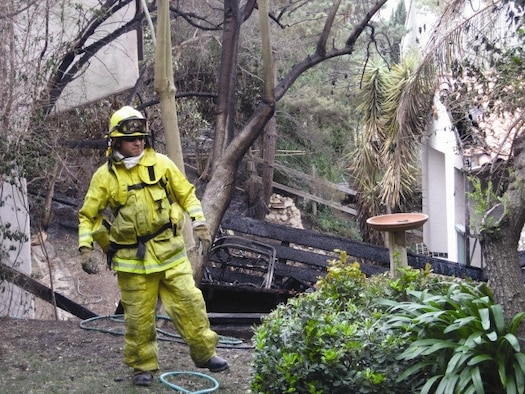 Fire fighter Dan Caballero provides structural protection at a residence in Malibu for the same fire. Four personnel from the March ARB Fire Department along with Engine-8 were sent to Malibu Nov. 8 - 10 to assist with the fires. The department, which falls under the 452nd Civil Engineering Squadron, has a dual mission supporting both the base as well as assisting the local community.  (U.S. Air Force photo)