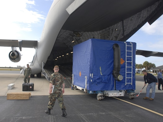 Air Force and contractor personnel observe as GPS satellite IIR-M 20, safely housed in its shipping container, is offloaded Jan. 10 at Cape Canaveral AFS. (U.S. Air Force photo by Tony Gray)