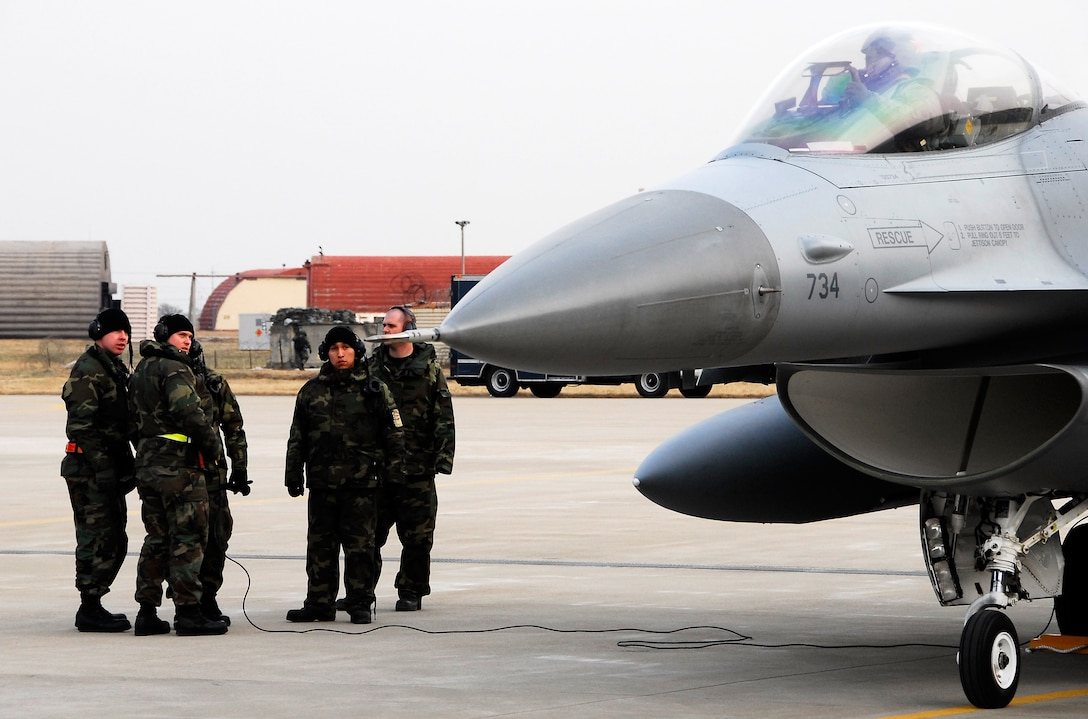 KUNSAN AIR BASE, South Korea -- Members of the 8th Aircraft Maintenance Squadron discuss in-flight errors with an 80th Fighter Squadron F-16 pilot after landing a F-16 Block 40 jet from Eielson Air Base, Alaska here Jan 18.  The 80th FS will be receiving 18 Common Configuration Implementation Program Block 40 jets from the Alaskan based unit and Eielson will in-turn receive the 80th FS Block 30 jets for an aggressor squadron.  (U.S. Air Force photo/Tech Sgt. Quinton T. Burris)