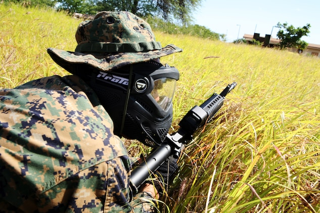 BARBERS POINT, Hawaii -- A member of Double Tap low crawls through tall grass in order to sneak up and secure a enemy tower during an airsoft competition held here Jan. 21.