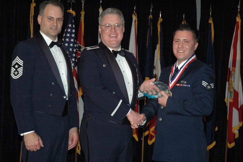 MCGUIRE AIR FORCE BASE, N.J. -- Senior Airman Mario J. Aochoa, right, of the 514th Communication Squadron receives the 514th Air Mobility Wing Airman of the Year 2007 Award from Col. James L. Kerr, middle, and Command Chief Master Sgt. Michael J. Ferraro, left, Jan. 12 during the 8th annual awards banquet. (U.S. Air Force photo/Senior Airman William P. O'Neil III)
