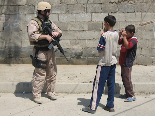Air Force Office of Special Investigations Special Agent Joshua Goodwin talks to Iraqi children while on patrol in Baghdad. AFOSI agents listen carefully and watch for clues, gathering information that will help them zero in on the insurgents they seek. (U.S. Air Force photo)