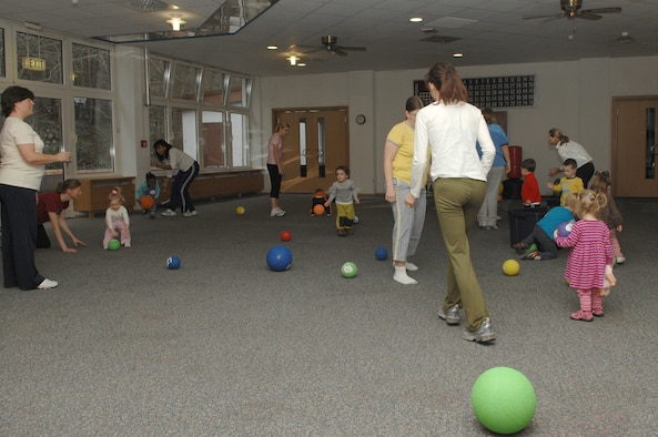 At the beginning of the Mommy and Me Yoga and Fitness class, playground balls are thrown throughout the room as the children hurry to pick them up and place them back in the bins, Jan.18, at the Vogelweh Community Center. This is one of the many activities done to get the children warmed up for the class. (U.S. Air Force photo by Senior Airman Megan M. Carrico) (RELEASED)