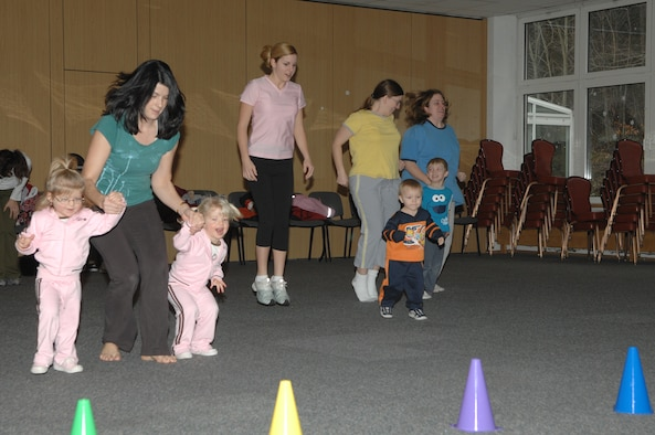 Kristine Toth and 2-year-old twins, Lydia and Lyla, (left), participate in a hopping activity at the Mommy and Me Fitness and Yoga class Jan.18 at the Vogelweh Community Center. (U.S. Air Force photo by Senior Airman Megan M. Carrico) (RELEASED)