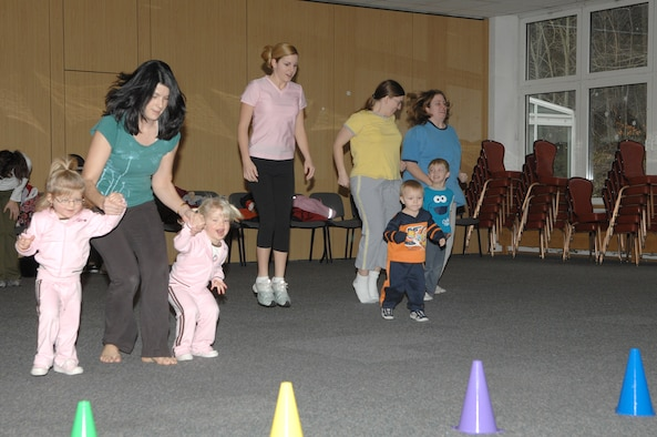 Kristine Toth and 2-year-old twins, Lydia and Lyla, (left), participate in a hopping activity at the Mommy and Me Fitness and Yoga class Jan.18 at the Vogelweh Community Center. (U.S. Air Force photo/Senior Airman Megan M. Carrico)