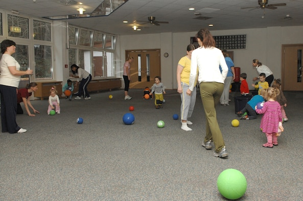 At the beginning of the Mommy and Me Yoga and Fitness class, playground balls are thrown throughout the room as the children hurry to pick them up and place them back in the bins, Jan.18, at the Vogelweh Community Center. This is one of the many activities done to get the children warmed up for the class. (U.S. Air Force photo/Senior Airman Megan M. Carrico)