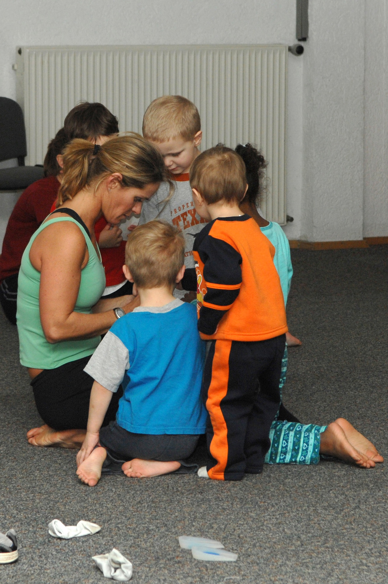 Renee Champagne, (left), hands out stickers to the children at the end of her Mommy and Me Yoga and Fitness class, Jan.18 at the Vogelweh Community Center. Ms. Champagne is the instructor for the class. (U.S. Air Force photo/Senior Airman Megan M. Carrico)