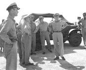 A second photo of General Spaatz and other dignitaries awaiting the return of the Enola Gay and her crew from mission to Hiroshima.