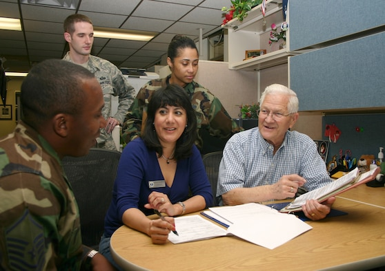 Bill Ward briefs exception to policy request cases he will turn over to his co-workers, (from left) Master Sgt. Cameron Jones, Tech. Sgt. Jeff Gilbert, Letty Inabinet and Tech. Sgt. Yahil Sanchez, prior to his retirement. (U.S. Air Force photo/Master Sgt. James Brabenec)
