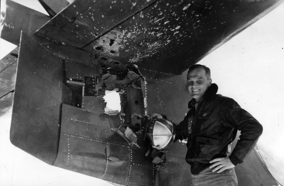 """John Glenn by the tail of his battle-damaged Marine Corps F9F """"Panther"""" during the summer of 1953. The plane had 714 holes in it from enemy shrapnel. (U.S. Air Force photo)"""