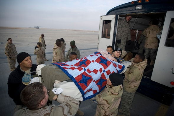 Army Pfc. William McClellan, an injured member of the 502nd Infantry Brigade, is unloaded from a Contingency Aeromedical Staging Facility bus on the Balad Air Base, Iraq, flight line Jan. 13 before departing for the Regional Medical Center Landstuhl, Germany. The CASF employs volunteers to assist with the loading and unloading of patients on litters. Private McClellan is deployed from Fort Campbell, Ky. (U.S. Air Force photo/Master Sgt. John Nimmo, Sr.)