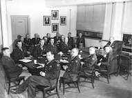 Staff Meeting in Major General Muir S. Fairchild's office. In attendance: Brig. Gen. Eugene L. Eubank, Lt. Col Albert S. Barnhart, Col Harold Bowman, Col Charles A. Horn, Col Erik H. Nelson, Col Otto P. Weyland, Lt. Col. Bream C. Patrick, Col David M. Schlatter, Maj. Henry C. Lint, Lt. Col. Brintall H. Merchant, Col Paul E. Ruestow, Col William F. McKee, Col Mervin E. Gross, Lt. Col. Leo I. Herman, Maj. Gen. Muir S. Fairchild, Col Lyman P. Whitten, Brig. Gen. Stuart C. Godfrey, and Lt. Col. Frederick L. Anderson, Jr.