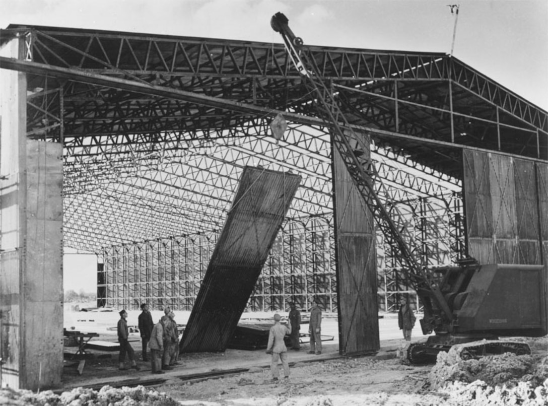 Members of an Engineer battalion building a hangar at an airdrome somewhere in England, swing a 1,500 pound door into place. 1943 (A-57785 A.C.)
