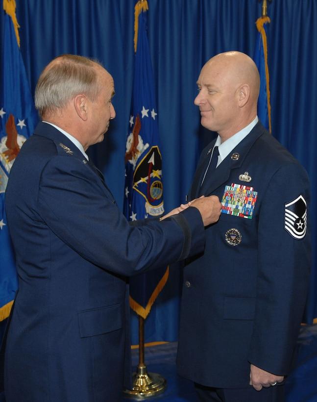 Master Sgt. Michael Garrison receives the Airmen's medal from SMC Commander Lt. Gen. Michael Hamel.