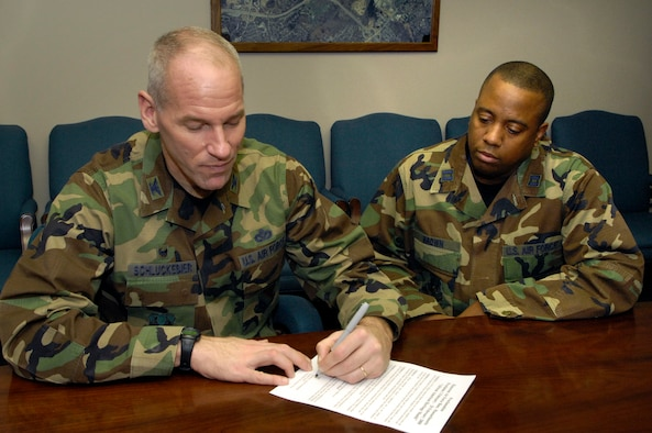 HANSCOM AFB, Mass. – Col. Tom Schluckebier (left), 66th Air Base Wing commander, signs the Black History Month proclamation while Capt. Robert Brown, 850th Electronic Systems Group looks on. Throughout February the base community is invited to attend the many events and activities planned to recognize and celebrate the achievements and contributions of black Americans. (U.S. Air Force photo by Mark Wyatt)