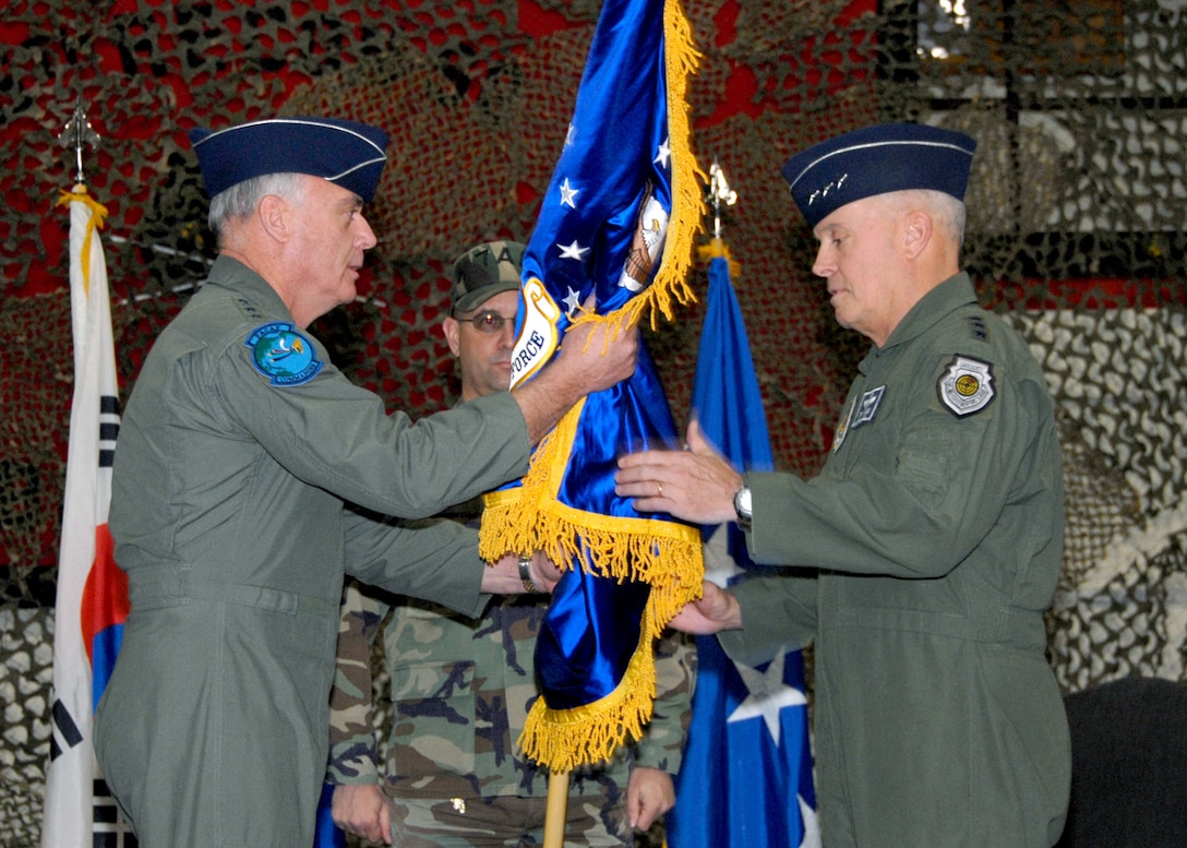 "OSAN AIR BASE, Republic of Korea -- (L to R) General Carrol H. ""Howie"" Chandler, Pacific Air Forces commander, passes the new Seventh Air Force (Air Forces Korea) guidon to Lt. Gen. Stephen G. Wood, Seventh Air Force (Air Forces Korea) commander, during the Seventh Air Force Re-designation Ceremony Jan. 30 in the 5th Reconnaissance Squadron hangar. This ceremony marks the implementation of the Chief of Staff of the Air Force's direction to establish an Air Force component organization that is structured to operate and train every day in its wartime configuration.  These warfighting organizations are being stood up around the globe to enable the effective command and control of air, space, and cyberspace forces conducting missions across the spectrum of military operations.  The new Seventh Air Force (Air Forces Korea) organization will provide the United States Forces Korea commander with critical air component capabilities, ensuring a key element of joint and combined operations on the Korean peninsula.  (U.S. Air Force photo/Staff Sgt. Lakisha Croley)"