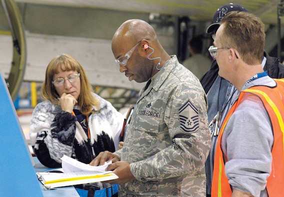 As Logistics Standardization and Evaluations Team inspector Senior Master Sgt. Terence Henderson reviews toolbox paperwork, Tinker Aircraft personnel wait to answer any questions during the Jan. 29 inspection in a Bldg. 3001 tanker dock.  Karen Prickett, Ricky Poole, back, and Ted Dexter, right, were just a few of the Tinker personnel across base who welcomed 64 inspectors into their shops. (Air Force photo by Margo Wright)