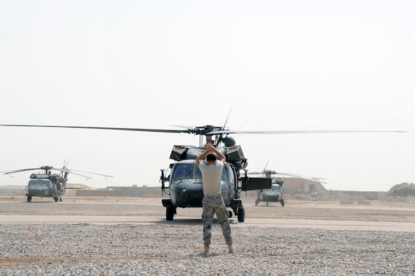 ALI BASE, Iraq -- Senior Airman Brian Pittman, transient alert specialist, signals an Army UH-60 Blackhawk to park here June 30. The Blackhawk is the Army's front-line utility helicopter used for air assault, air cavalry, and aeromedical units. The transient alert team coordinates the safe arrival and departure of aircraft on a daily basis. Airman Pittman is deployed to the 407th Expeditionary Operations Support Squadron from Tyndall AFB, Fla. (U.S. Air Force photo/Tech. Sgt. Sabrina Johnson)