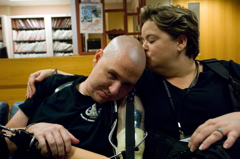 Matt's life has transformed into a constant juggling act of medical appointments and long stints in hospital  waiting rooms, but Annette has been at his side through it all- even to provide a tender kiss or two. (photo by Tech. Sgt. Matthew Hannen)