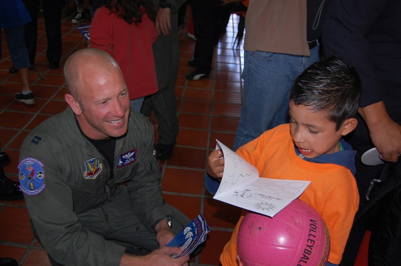 Capt. Sam Joplin, the F-15 West Coast Demonstration Team pilot, observes a child's reaction upon receiving a coloring book from visiting Airmen.  Airmen visited and ate lunch with staff and children at the ALDEAS SOS home near Medellin, Colombia during planned community outreach events associated with the RIO NEGRO air and trade show.  More than 25 Airmen gave presents of books, candy, stickers and photos to the orphans; then signed autographs and invited the group to the air and trade show the following day. (Photo by Capt. Nathan Broshear)