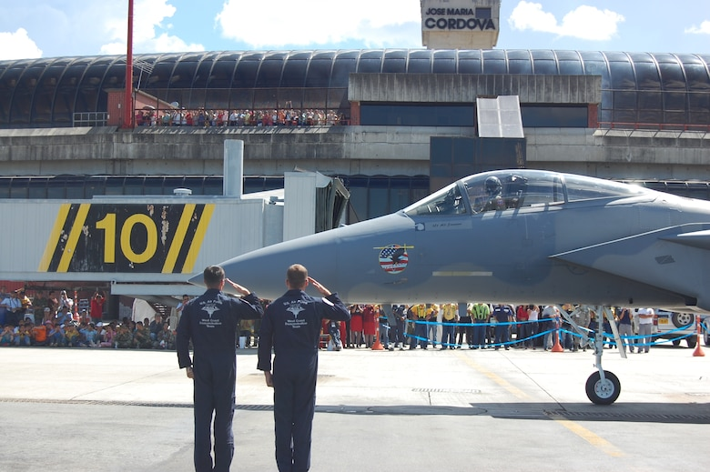 Members of the F-15 West Coast Demonstration Team salute the departing F-15C Eagle, flown by Capt. Sam Joplin, during the pre-flight portion of the team's demonstration at the RIO NEGRO air and trade show venue in Medellín, Colombia. The Demonstration Team celebrated 25 years of service during RIO NEGRO by performing for audiences at the Medellín International Airport for six days, thrilling an audience estimated at more than 100,000 Colombian citizens. (Photo by Capt. Nathan Broshear)