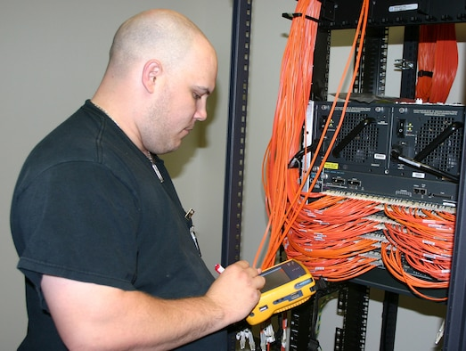Gregory Campbell, a network data communication analyst at the Air Force Personnel Center here, verifies cable ports for the new operation center's network switch.  The switch's components feed down from a secure server and will give AEF workers secure lines once the operation center is fully operational.  Since November 2007, more than 12,000 feet of combined fiber optic and copper cables have been placed in the new center. (U.S. Air Force photo/Richard Salomon)