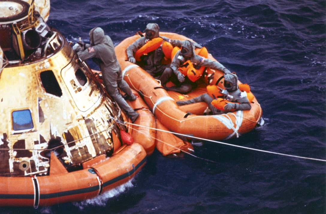 Air Force pararescueman Lt. Clancy Hatleberg closes the Apollo 11 spacecraft hatch as astronauts Neil Armstrong, Michael Collins and Buzz Aldrin, Jr., await helicopter pickup from their life raft. They splashed down at 12:50 pm EDT July 24, 1969, 900 miles southwest of Hawaii after a successful lunar landing mission. The command module moved from Patrick Air Force Base, Fla. July 1 was used by pararescuemen to train for both the Apollo and Skylab programs. (photo/NASA)
